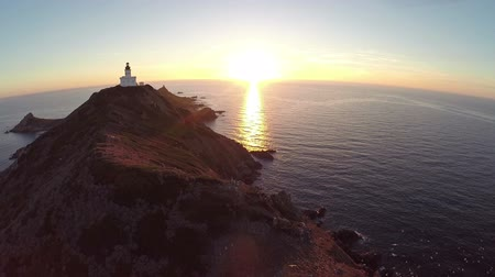 takeoff area : Flight over the sea and islands with lighthouse at sunset, Ajaccio area, Corsica, France. Aerial panoramic view. Stock Footage