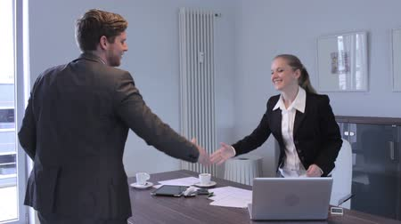 kézi : Two businesspeople, a man and woman, seated at a desk in an office shaking hands on the acceptance and closure of a business deal or transaction
