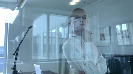s rukama zkříženýma : View of a businesswoman standing with folded arms through an interior glass partition in an office