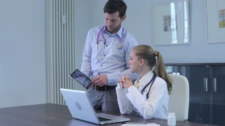 physicians : Two young doctors having a discussion with the woman seated at her desk in her office looking at information on the screen of the tablet-pc held by her male colleague