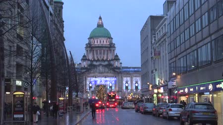 belfast : Traffic and people walking in front of City Hall of Belfast, decorated with Christmas lights, Northern Ireland, United Kingdom. Tourism and travel destination, city monument with Christmas market