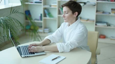 организации : office worker girl in a spacious office working with laptop