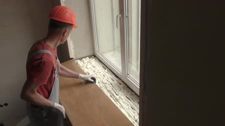 installation lectrique : Worker is installing a window on a polyurethane foam. Stock Footage