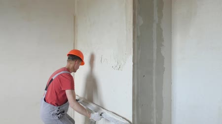 plasterer : Worker is putting a gypsum plaster on a wall. He is using a long ruler.