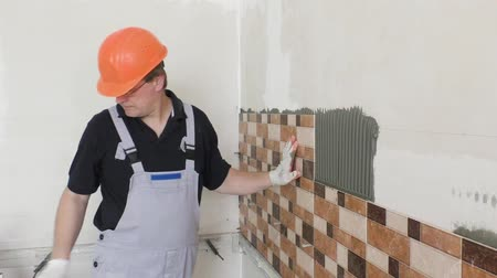 installation lectrique : The worker is installing the ceramic tile on the wall. Stock Footage