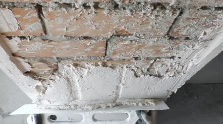 plasterer : Worker is putting a gypsum plaster on a brick wall.