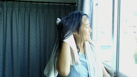 side window : slow motion of woman wipe hair by towel at window side Stock Footage