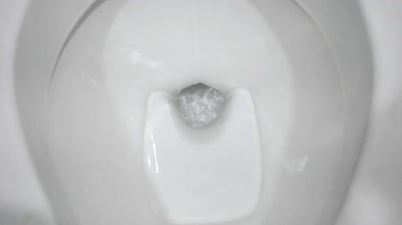 заподлицо : Closeup of a flushing toilet. The water swirls in the toilet bowl.