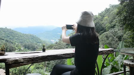 dinlenmek : Travel woman enjoy scene and take a photo of mountain view