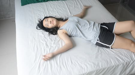 pizsama : woman with pajamas slowly laying down on bed , relax concept