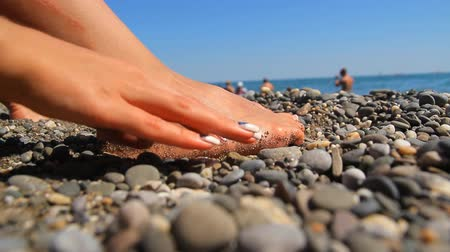 релаксация : Feet on a rocky seashore The legs on the sea beach, the hand touches the pebbles