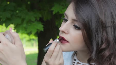 ruj : Beautiful girl doing makeup with lipstick Stok Video