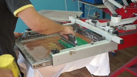 printings : Screen printing manufacturing on t-shirts. Worker print an image on fabric on a hand bench. Slow motion camera