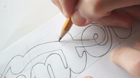 ołówek : Lettering or logo creating with a pencil on white paper. Handlettering design creation process. Designer drawing letters with pen. Sketch artwork with liner marker. Calligraphy work.