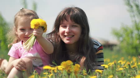 Mom and daughter throw their bouquet of dandelions Stock Footage