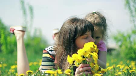 Daughter gives mom smell the bouquet of dandelions
