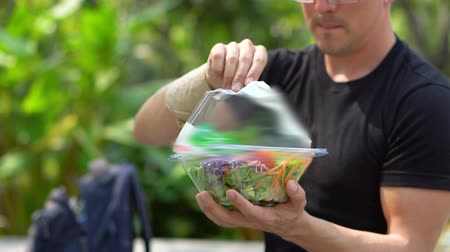 малая глубина резкости : Opening Lid of Salad in Plastic Take Away Container in Park