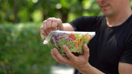 fedél : Opening Lid of Take Away Salad in Plastic Container in Park Stock mozgókép