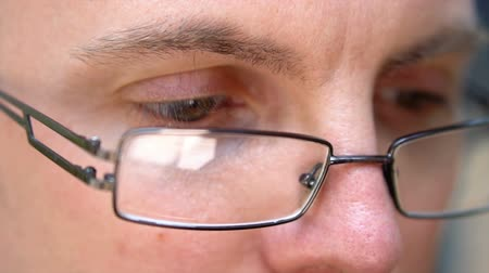 малая глубина резкости : Glasses and Eye Close up of Focussed Caucasian Man With Glasses Reading