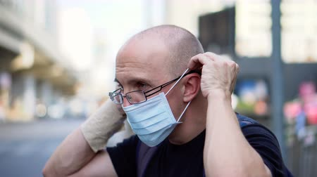 szűrés : Putting on Mask To Protect Against Hazardous Air Pollution Of Exhaust Fumes Of Big City Stock mozgókép