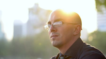 рукав : Shaky Handheld Slowmo Side View Portrait Of Late 20s Man With Glasses Sitting in Park With Sun Backlighting Стоковые видеозаписи