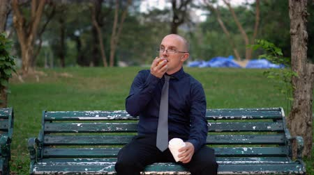 рукав : Office Worker With Coffee Cup in Hand Eating Healthy Apple On Bench Outside