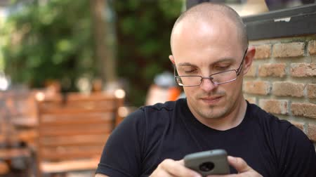 малая глубина резкости : Cinematic Shallow Depth Of Field Moving Shots - Close up of Moderately Attractive Balding Caucasian Man Texting and Browsing using Smartphone in Outdoor Cafe - 2 Angles