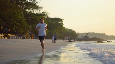 sprintel : Young Man Running On Exotic Beach During Sunset Slow Motion - Jogging and Healthy Lifestyle Stock mozgókép