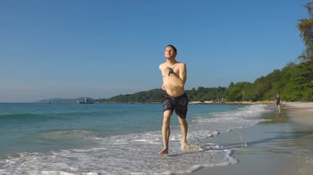 follow shot : Handsome Young Man Jogging on Tropical Beach - Excercising and Maintaining Healthy Lifestyle While Traveling