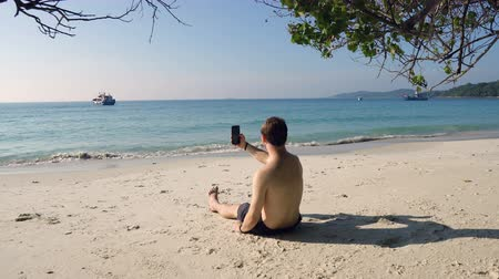 expat : Traveler Sitting on Tropical Beach and Using Phone