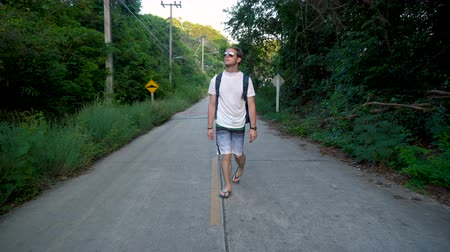 yemyeşil bitki örtüsü : Caucasian Backpacker Walking Alone on Empty Road in Southeast Asian Tropical Jungle
