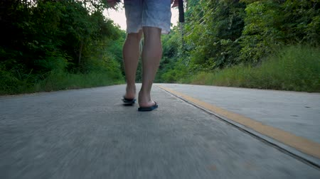 follow shot : Low Angle Follow Shot of Tourist With Flip Flops Walking in Middle of Road in Jungle