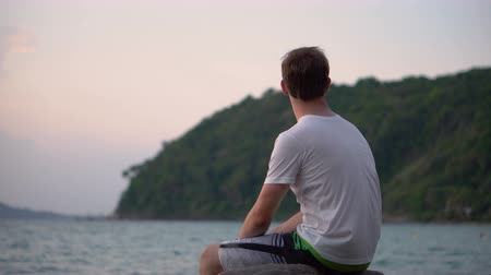 özlem : Sorrowful Sad Young Man Sitting By Tropical Beach Looking At Ocean