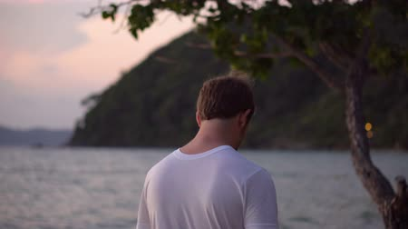 sutil : Handsome Young Caucasian Man Overlooking Tropical Ocean During Sunset