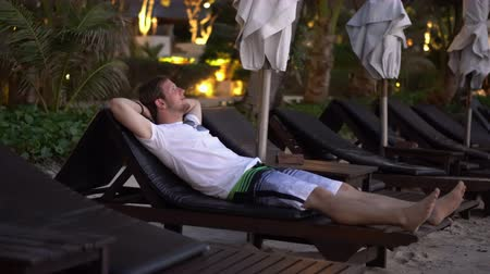 magánélet : Man on Vacation Laying on Lounger at Resort Beach in Evening