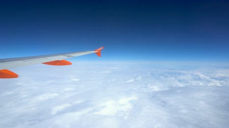 curvature : View Outside Window of Commercial Aircraft While Flying at Cruise Altitude on Sunny Day With Cloudscape Below Stock Footage