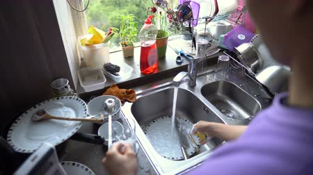 sabão : Asian Man Washing Dishes in Kitchen at Home Stock Footage