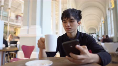 food court : Young Asian Man Drinks Hot Beverage in Cafe or Restaurant And Texting on Phone While Smiling