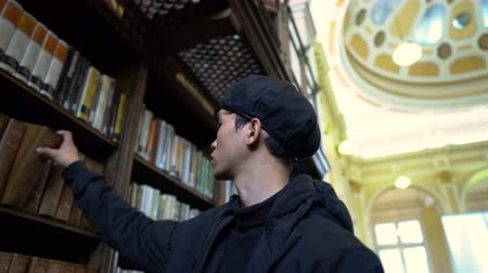 classici : Man Searching Through Old Library To Find Book And Then Reads It