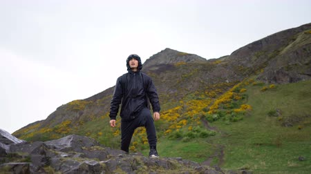 último : Young Man HIking During Bad Rainy Weather Portrait in Scottish Highlands