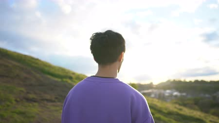 lookout point : Follow Shot of Young Asian Man Walking To Scenic Lookout Point on Hill And Looking at Landscapeaac Stock Footage