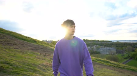 Portrait Gimbal Shot of Young Asian Man Walking Outdoors in Nature With Sun in Background