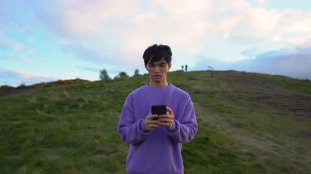 conectados : Dolly Out Portrait of Young Millennial Asian Man Texting Using Smartphone While Standing in Outdoor Nature Environment - Smartphone Addiction Archivo de Video