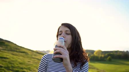 jarmuż : Smiling Attractive Woman Drinking Healthy Green Vegetable Smoothie in Outdoor Nature Scenery During Sunset Wideo