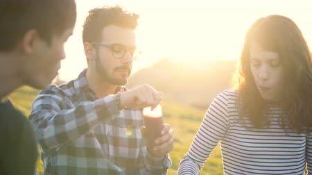 sharing : Attractive Young Friends Chatting and Sitting Outdoors in Nature Sharing Healthy Food and Laughing Together During Sunset Stock Footage