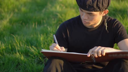 focussed : Asian University Art Student Wearing Beret Sketching Landscapes and Drawing in Notebook Outdoors in Nature