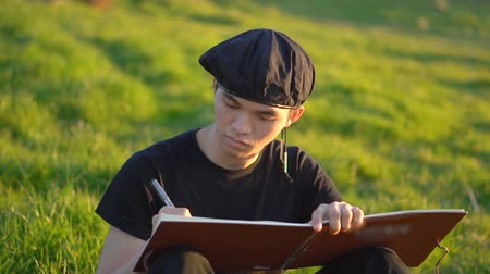 notizblock : Asian University Art Student Wearing Beret Sketching Landscapes and Drawing in Notebook Outdoors in Nature