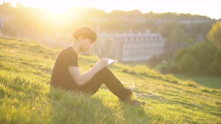 reference : Young Art Student Drawing an Sketching in Notebook Using Pen While Being Outdoors in Nature During Vibrant Sunset