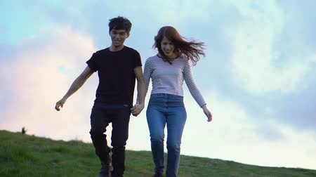 follow shot : Slow Motion Happy Mixed Ethnicity Couple Running Down Hill While Holding Hands Stock Footage