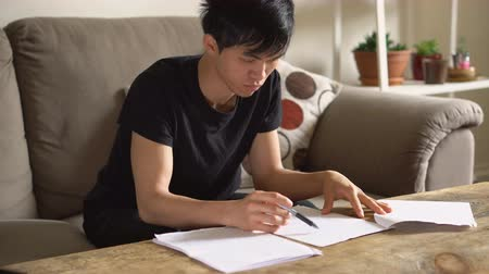 notas : Asian College Student Doing Homework in Living Room